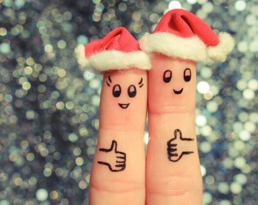 Finger art of couple celebrates Christmas. Concept of man and woman laughing in new year hats. Happy pair showing thumbs up. Toned image.